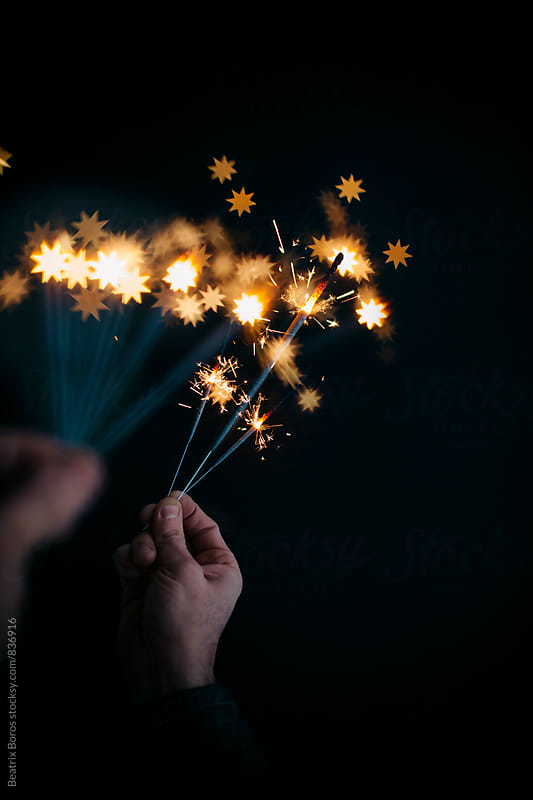 Man's both hands with sparklers, the further ones creating heart shaped bokeh by Beatrix Boros for Stocksy United