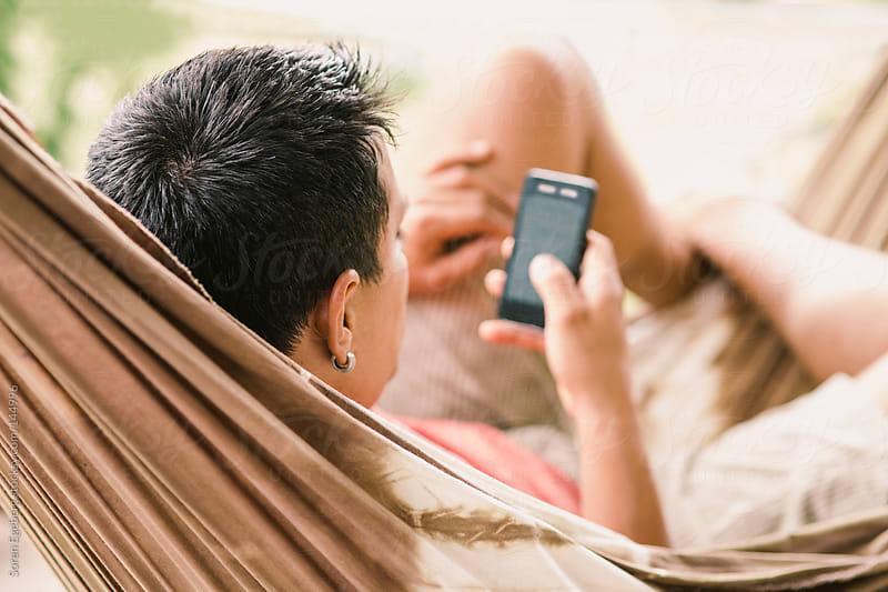 Man lying in hammock using mobile smart phone for messaging. by Soren Egeberg for Stocksy United