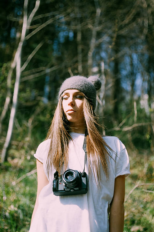 A portrait of young woman in a funny hat in the forest with old analog camera by Anna Malgina for Stocksy United