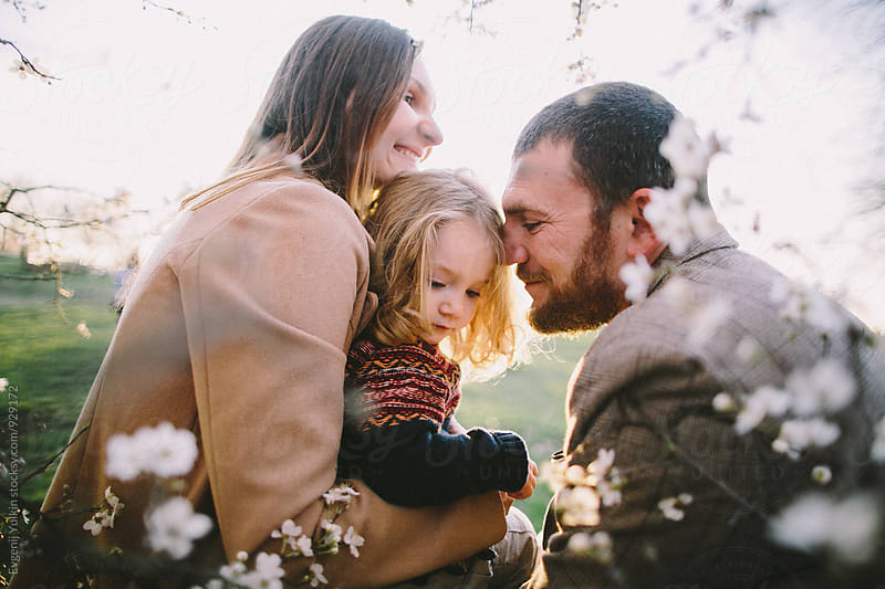 Family feeling happy together under the bloomed tree by Evgenij Yulkin for Stocksy United