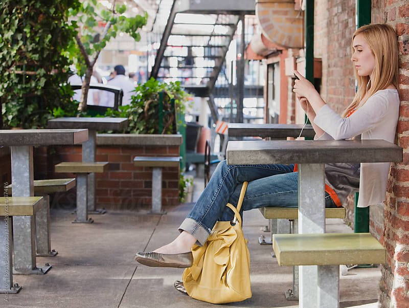 Young woman listening to music at outdoors cafe by Andersen Ross Photography for Stocksy United