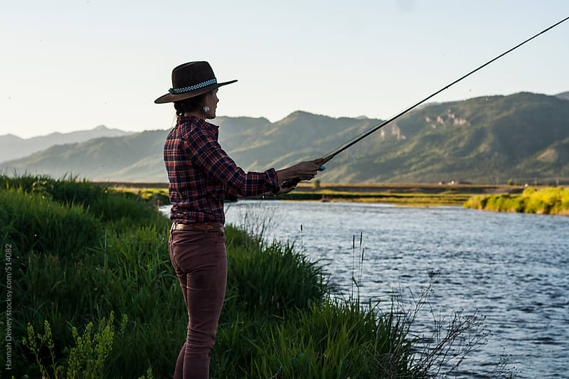 Woman spends a summer evening fly-fishing on the Salt River in Wyoming by Hannah Dewey for Stocksy United