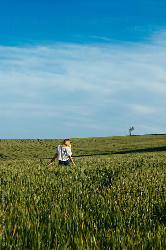 Woman walking alone through a field of wheat by Susana Ramírez for Stocksy United