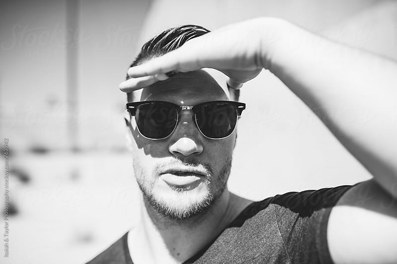 Man looking in camera with glasses  by Isaiah & Taylor Photography for Stocksy United
