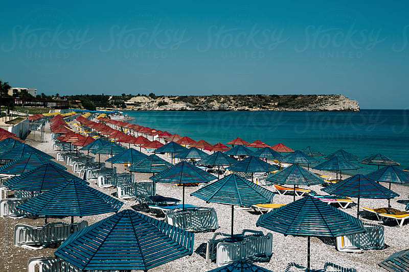 Blue and red parasols along the beach by Paul Phillips for Stocksy United