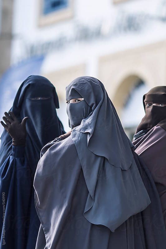 traditional Muslim women in North Africa, religious believers in the Medina,looking at the camera by Igor Madjinca for Stocksy United
