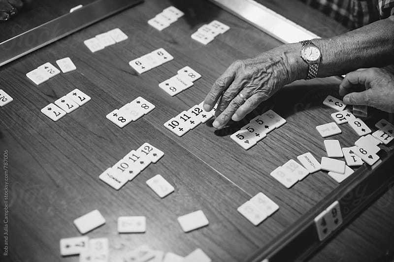 Detail of elderly man's playing rummy by Rob and Julia Campbell for Stocksy United