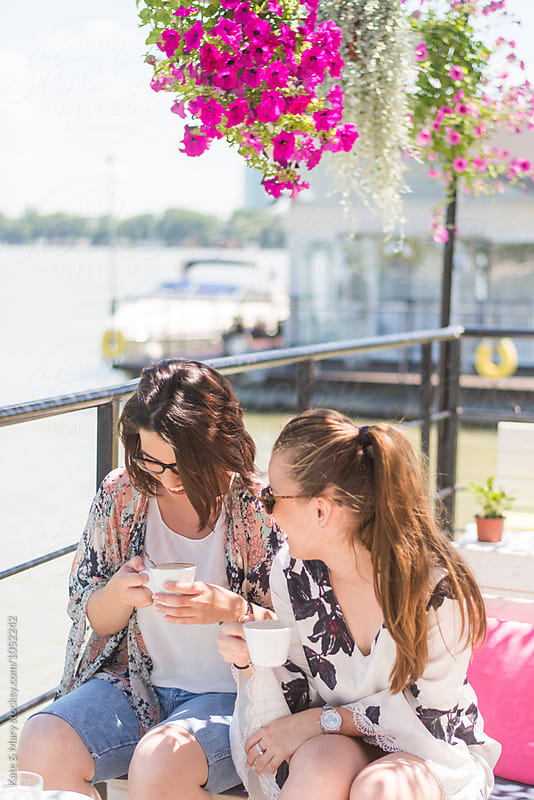 Two best friends enjoying on sunny day and drinking coffee by Katarina Simovic for Stocksy United