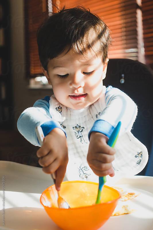 Toddler boy eating breakfast by Lauren Naefe for Stocksy United