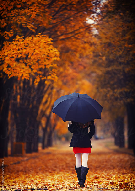 Young woman with umbrella walking in autumn park alone by Ilya for Stocksy United