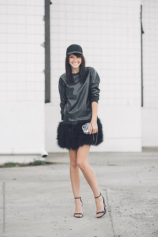 A street style photo of a young woman smiling at the camera by Ania Boniecka for Stocksy United
