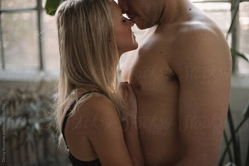 Young shirtless man kissing girlfriends forehead in industrial loft by Daring Wanderer for Stocksy United