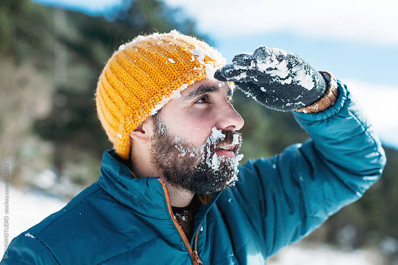 Young bearded man covered with snow looking at a beautiful landscape. by BONNINSTUDIO for Stocksy United