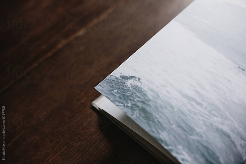 detail of ocean image in open book by Nicole Mason for Stocksy United