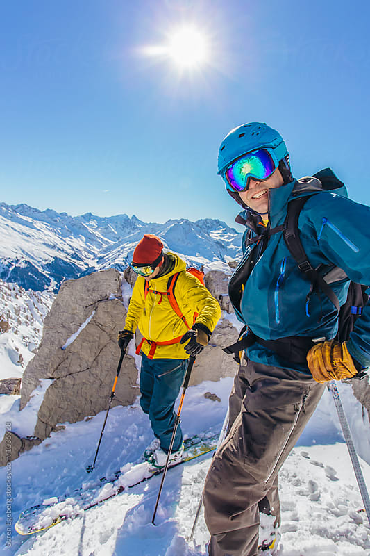 Two skiers on top of a mountain by Soren Egeberg for Stocksy United