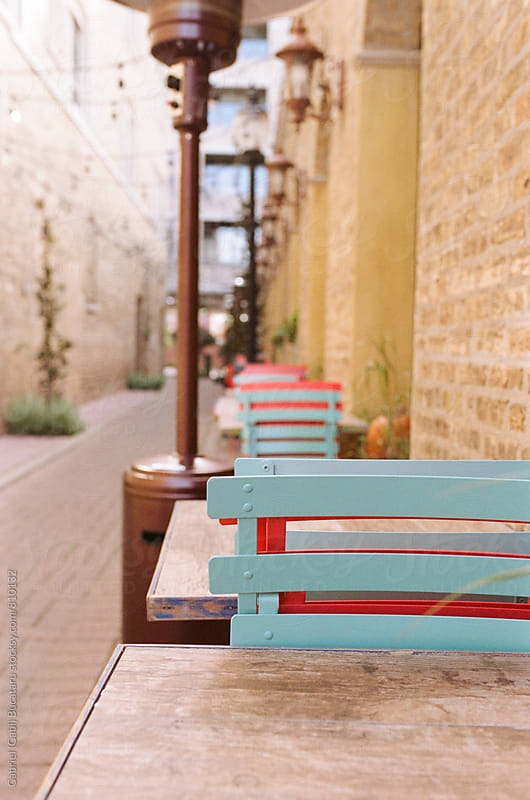 Tables and chairs in an alley by a restaurant by Gabriel (Gabi) Bucataru for Stocksy United