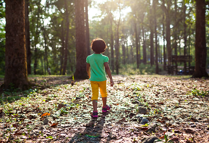 Child walking on a forest path at afternoon by Saptak Ganguly for Stocksy United