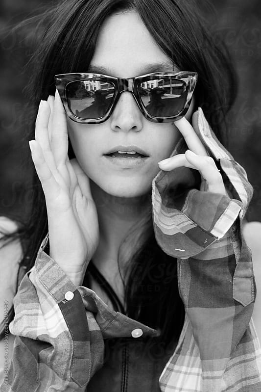 A portrait of a woman holding sunglasses to her face by Ania Boniecka for Stocksy United