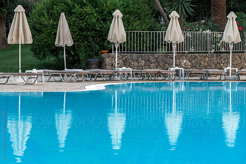 Early evening by a swimming pool with still water and sun umbrella's. by Paul Phillips for Stocksy United