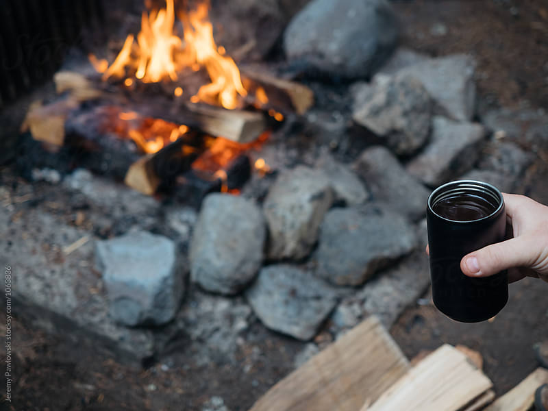 Coffee in mug held near campfire in National Park, Washington. by Jeremy Pawlowski for Stocksy United