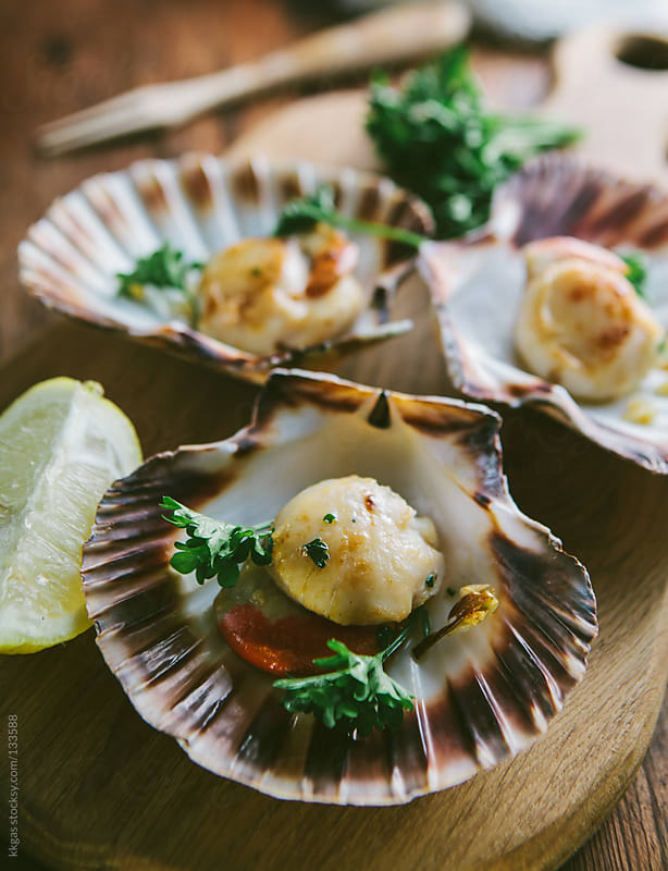 Scallops with parsley and lemon wedge. by kkgas for Stocksy United