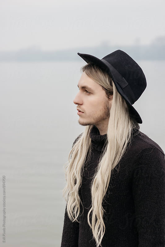 Portrait of a male model with long hair and black hat near river  by Evil Pixels Photography for Stocksy United