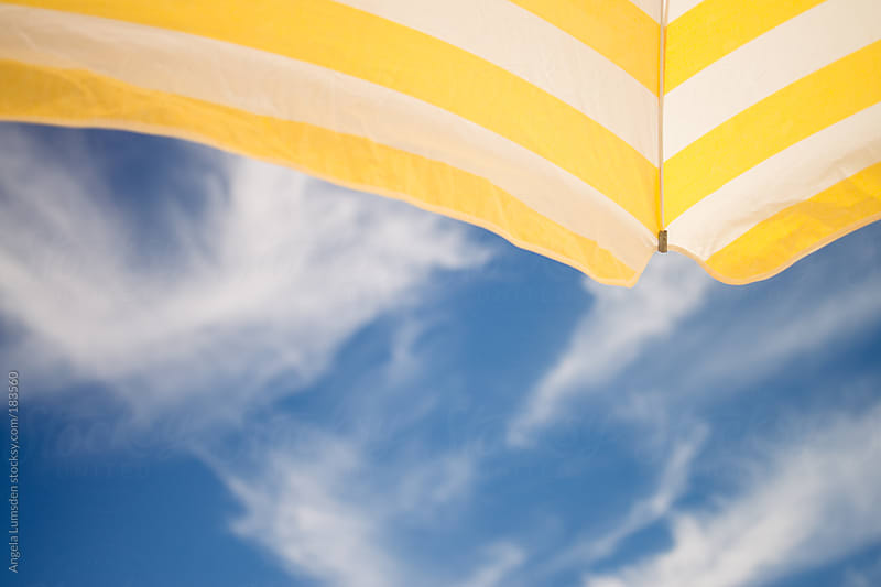 View from under a beach umbrella on a summer day with neat clouds by Angela Lumsden for Stocksy United