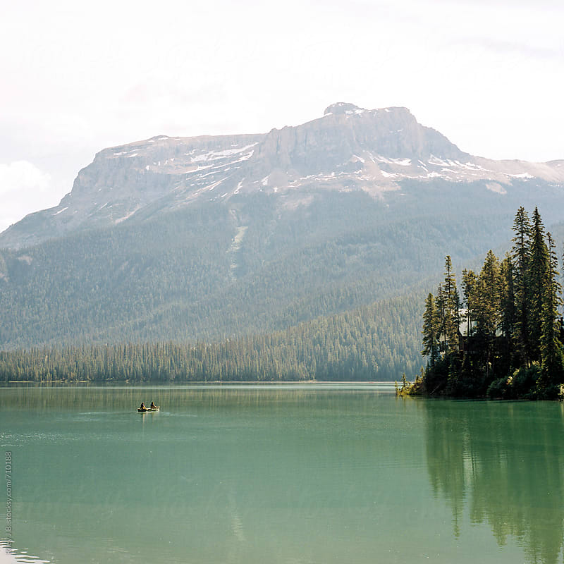 Canoe in a mountain lake passing a wooden island by Riley Joseph for Stocksy United
