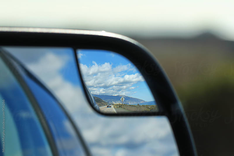 Road, sky and clouds in rear view mirror by Monica Murphy for Stocksy United