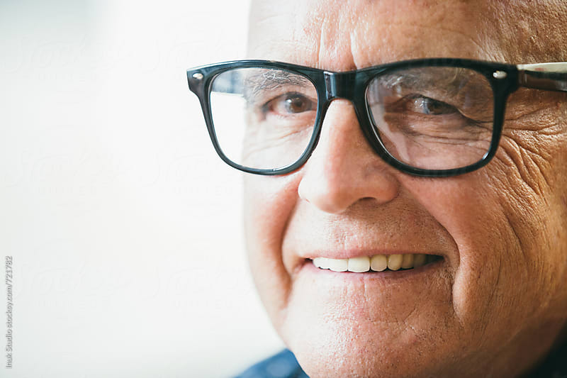 Senior stylish man smiling closeup portrait wearing glasses by Inuk Studio for Stocksy United