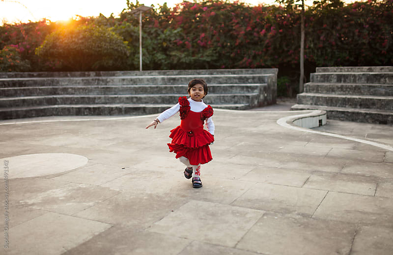Cute toddler in red dress playing in an open air theater by Saptak Ganguly for Stocksy United