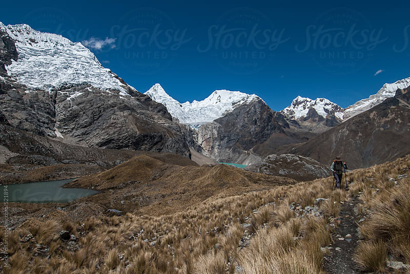 Hiker ascends a trail with dramatic high altitude peaks behind by Mick Follari for Stocksy United