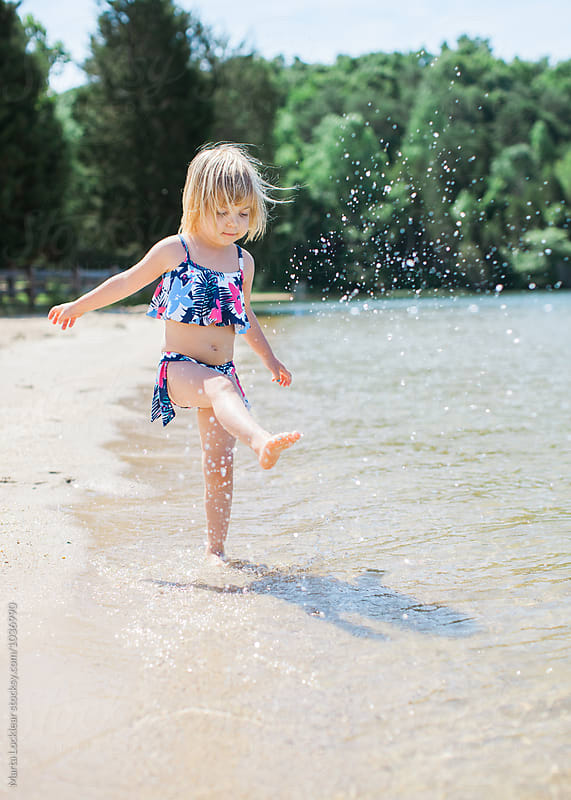 Little girl splashing in the lake water by Marta Locklear for Stocksy United