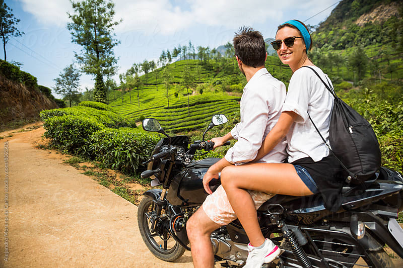 Young couple on a bike taking a ride through tea garden plantations by Alejandro Moreno de Carlos for Stocksy United