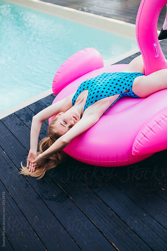 Beautiful young woman in a pool sitting on a Big Pink Flamingo by Jovana Rikalo for Stocksy United