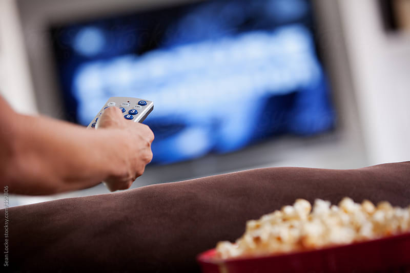 Television: Focus on Woman Holding Remote by Sean Locke for Stocksy United