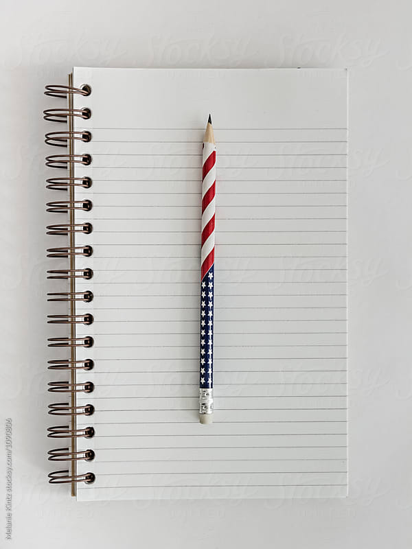 Open blank notebook with a stars and stripes pencil by Melanie Kintz for Stocksy United