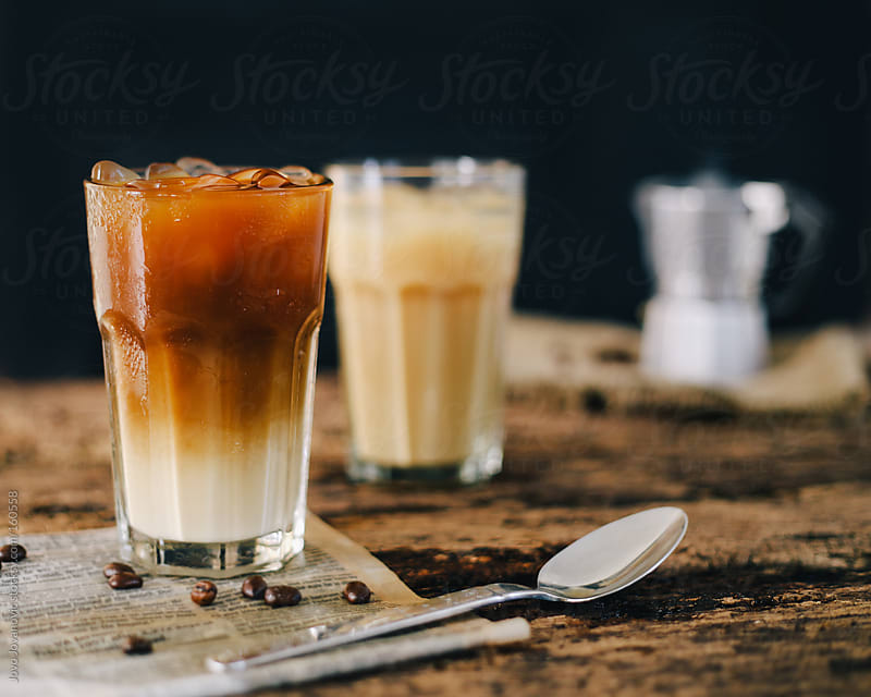 Mocha and white iced coffee on wooden table by Jovo Jovanovic for Stocksy United