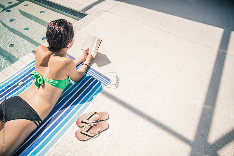 Attractive Healthy Woman Reading a Book by the Pool by suzanne clements for Stocksy United