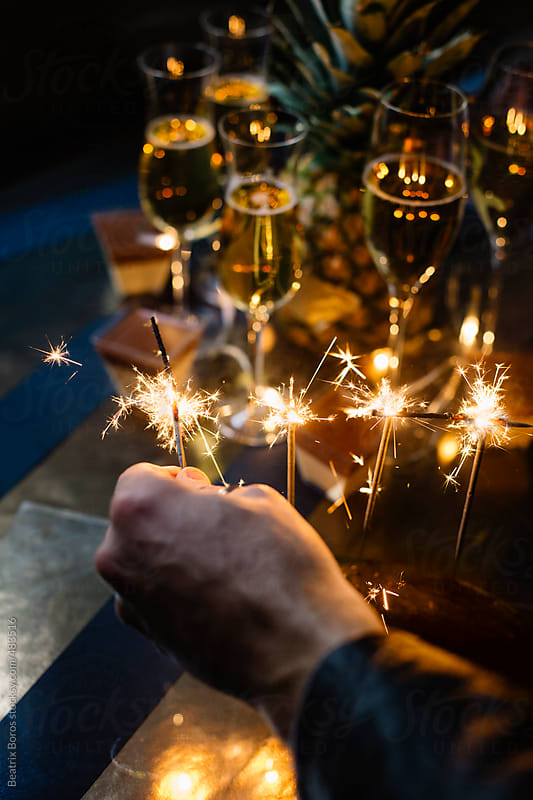 Man's hand sets on fire some sparkles for celebration by Beatrix Boros for Stocksy United