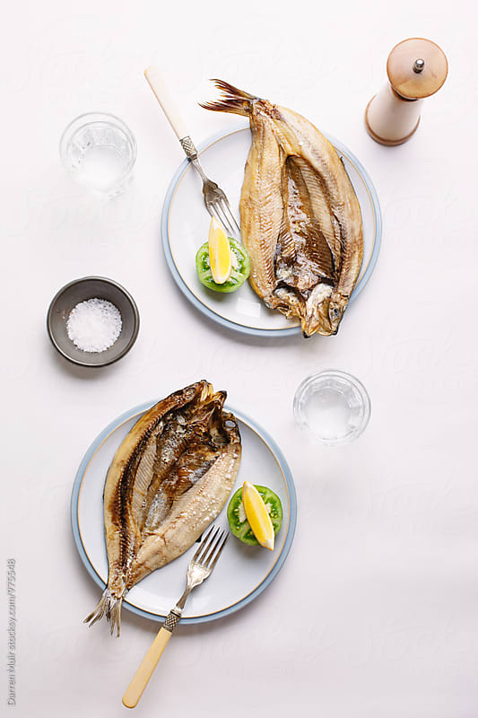 Grilled fish on plates with lemon. by Darren Muir for Stocksy United