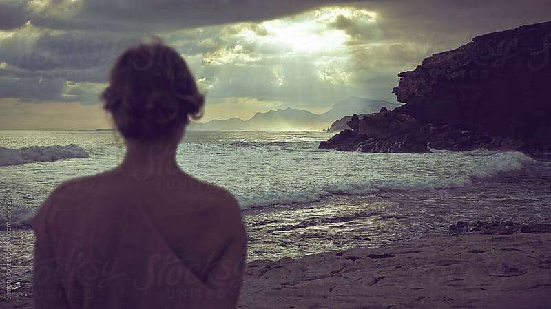 Woman by the Sea watching sunrays through cloudy sky by Simon Bolz for Stocksy United