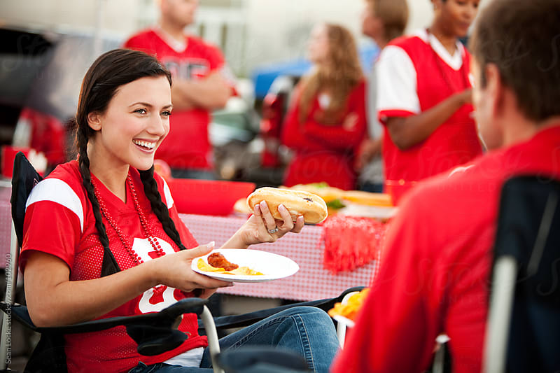 Tailgating: Woman Laughing and Eating Hot Dog by Sean Locke for Stocksy United