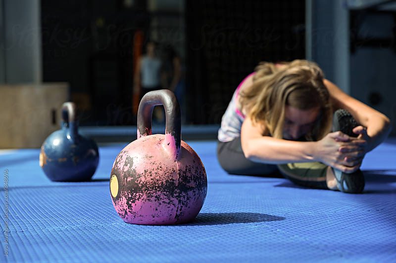 Blonde girl stretching, with kettlebells by her side by Jovo Jovanovic for Stocksy United