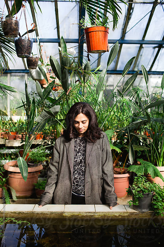 Woman looking down into water in a greenhouse. by Julia Forsman for Stocksy United