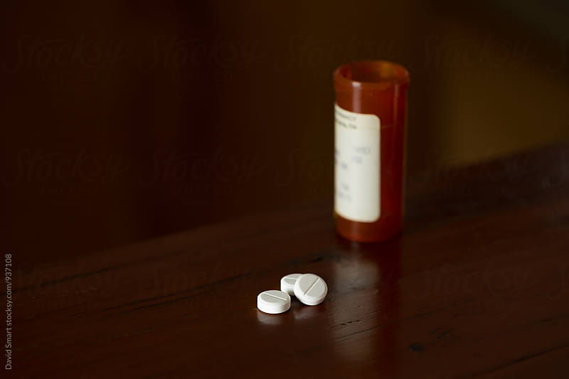 Prescription painkillers, oxycodone, lying on a wooden table with prescription medication bottle in the background. by David Smart for Stocksy United