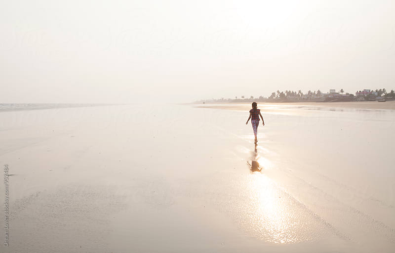 A lonely girl walking on a sea beach by PARTHA PAL for Stocksy United