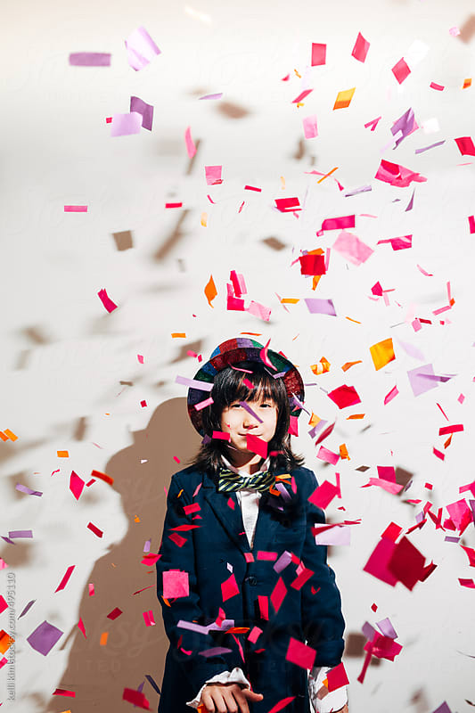 Young boy celebrates with colorful confetti by kelli kim for Stocksy United
