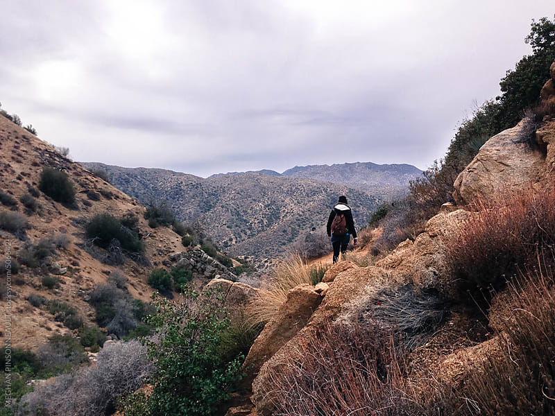 Woman Hiking Through Desert Mountains by MEGHAN PINSONNEAULT for Stocksy United