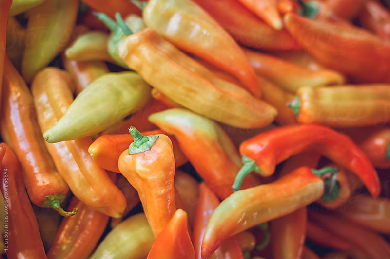 Orange and yellow peppers at the local market by Helen Sotiriadis for Stocksy United